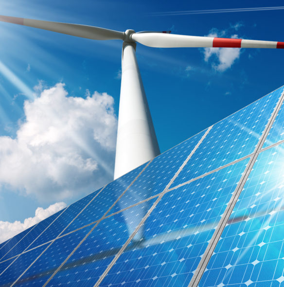 Group of solar panels and a wind turbine on a blue sky with clouds and sun rays. Solar and wind energy